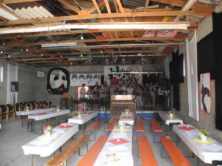 Halle mit Festzeltbänken, geschmückt, Chor steht auf der Bühne, keine Gäste
