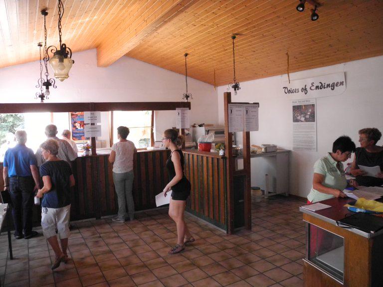 Vereinsraum ohne Tische und Stühle, Küchenbereich durch eine Bar abgetrennt