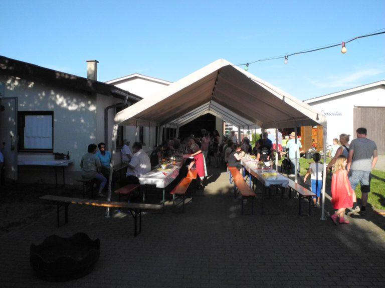 großes Zelt rechts neben der Musik-Schiire mit Festzeltbänken und Gästen