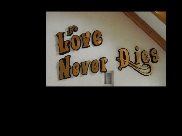 """Schild mit Aufschrift """"Love never dies"""""""