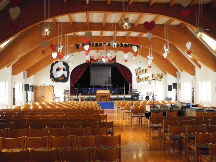 """Bürgersaal, Blick über die leeren Stuhlreihen zur Bühne. Links der Bühne hängt überdimensional die Maske, die das Phantom der Oper trägt, rechts das Schild """"Love never dies"""". Von der Decke hängen weiße und rote Herzen."""
