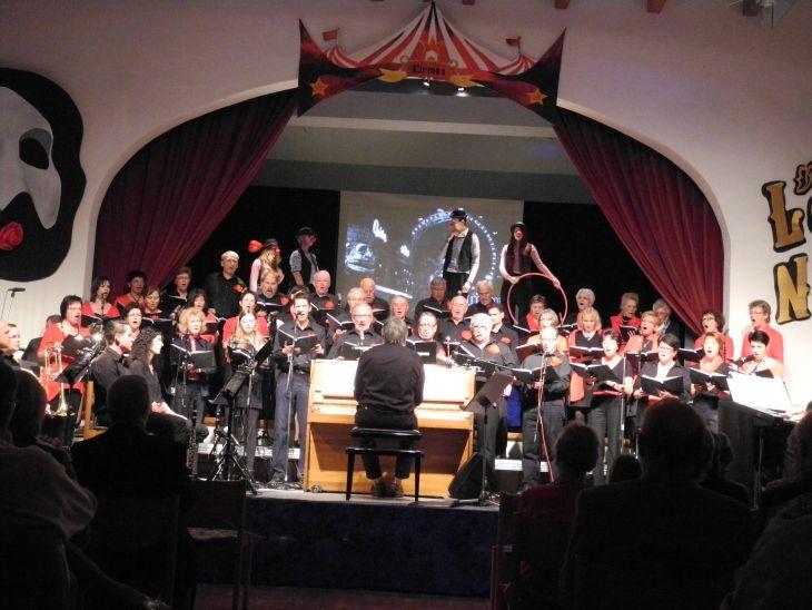 Chor, im Hintergrund vier Personen mit roter Clowns-Nase