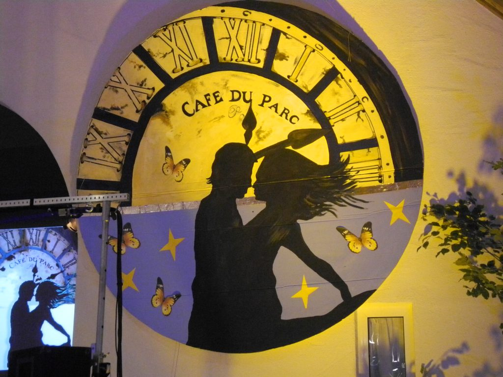 """riesiges Zifferblatt mit der Aufschrift """"Café du Parc"""". Im Vordergrund die Silhouette eines tanzenden Paares"""
