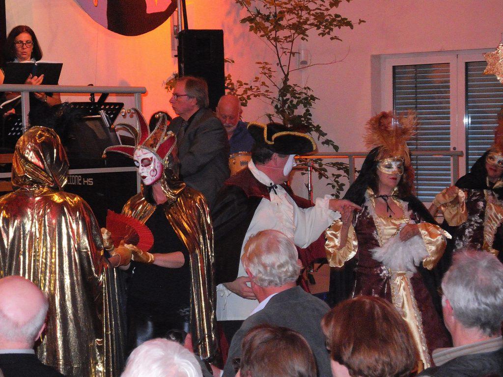 Maskenball: Das Phantom tanzt mit einer Dame im dunklen Kapuzen-Umhang, mehrere Damen in goldenen Umhängen und Masken vor dem Gesicht stehen dabei