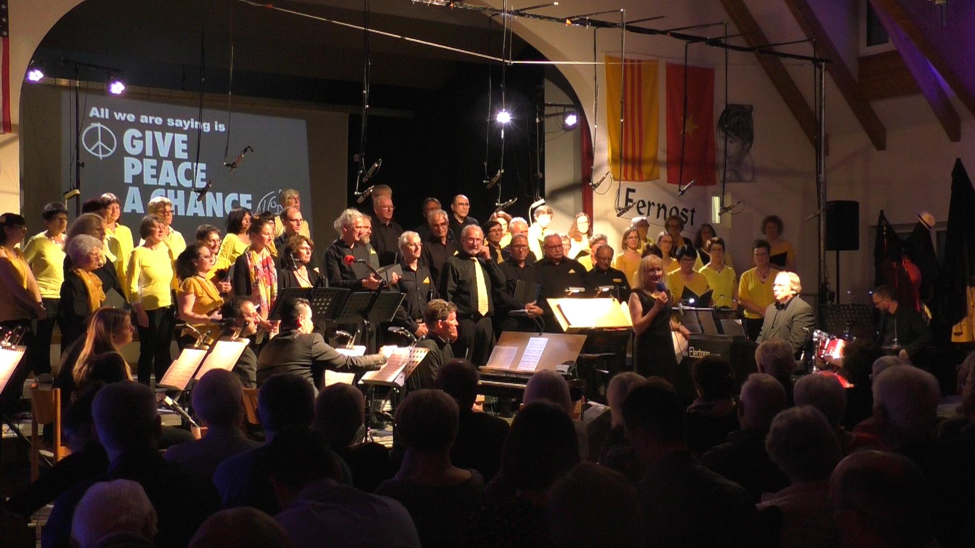 """Vorstandssprecherin Jacqueline Bieringer vor dem Gesamtchor, Hintergrund auf der Leinwand """"All we are saying is Give peace a chance"""""""